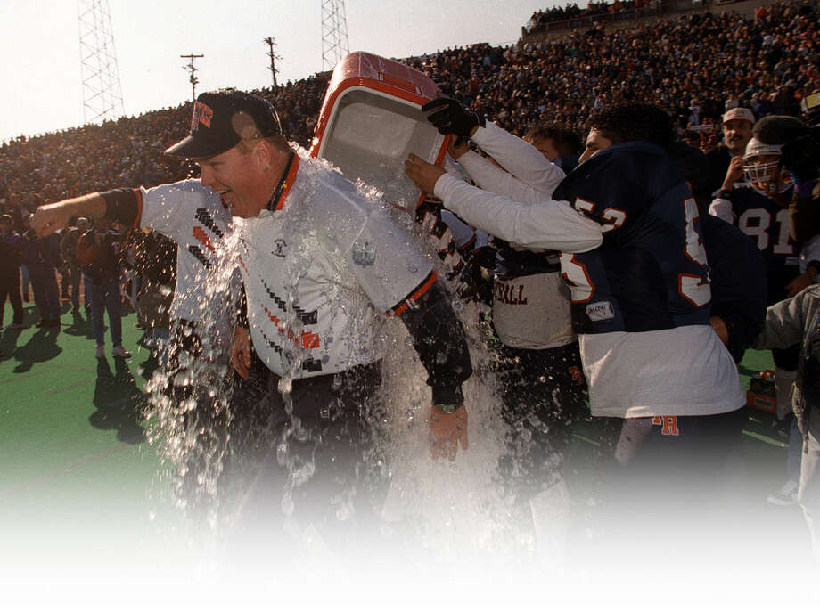 Roosevelt coach Bryan Dausin gets doused with ice water after the Rough Riders beat Flower Mound Marchs for the 1995 state title on Dec. 23 at Alamo Stadium. Photo: Express-News File Photo / SAN ANTONIO EXPRESS-NEWS
