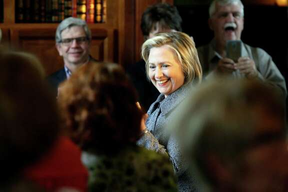 Democratic presidential candidate Hillary Rodham Clinton smiles as she is greeted before speaking at a gathering at the home of Dean Genth and Gary Swenson, Monday, May 18, 2015, in Mason City, Iowa.