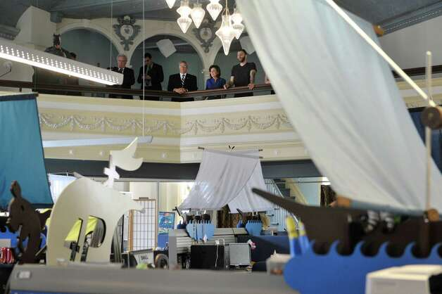 Troy Mayor Lou Rosamilia, left, New York State Lt. Governor Kathy Hochul, center, and  Justin Candeloro, an engineering group manager at 1st Playable Productions look out over the work floor from a balcony at 1st Playable Productions on Monday, May 18, 2015, in Troy, N.Y.  Lt. Governor Hochul was given a tour of the business.  (Paul Buckowski / Times Union) Photo: PAUL BUCKOWSKI / 00031882A
