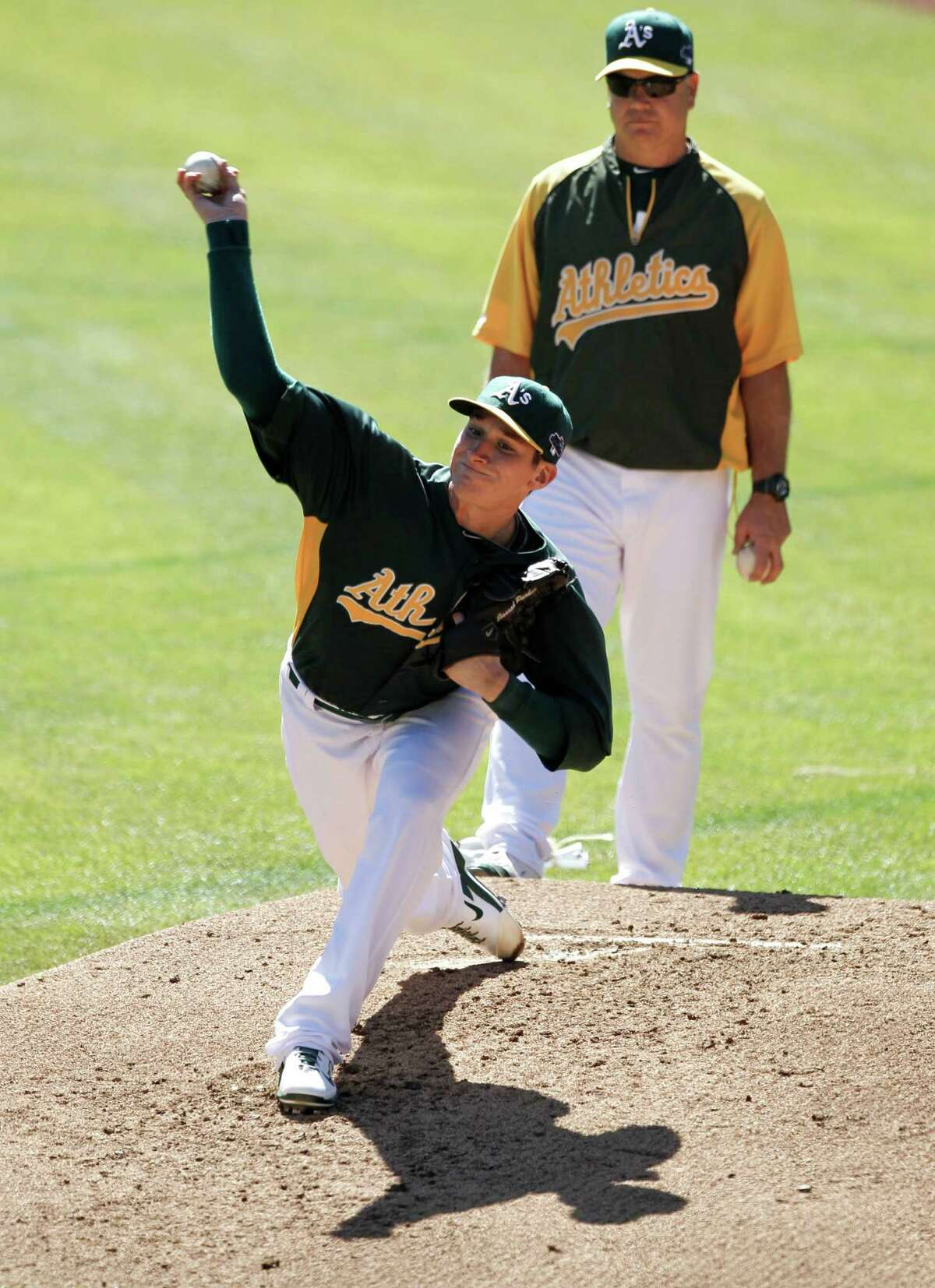 A's pitcher, Jarrod Parker, (11) throws under the watchful eye of pitching coach Curt Young, as the Oakland Athletics work out on Thursday Oct. 3, 2013, in Oakland, Calif. at O.co Coliseum. The Oakland Athletics and the Detroit Tigers prepare for tomorrow's opening game in the MLB American League Divisional Series.