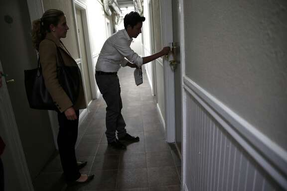 As Megan Filly, Deputy Press Secretary, Superior Court of California, looks on, Krista Gaeta, Deputy Director or Tenderloin Housing Clinic, enters a room at Drake Hotel in San Francisco, Calif., on Monday, May 18, 2015.
