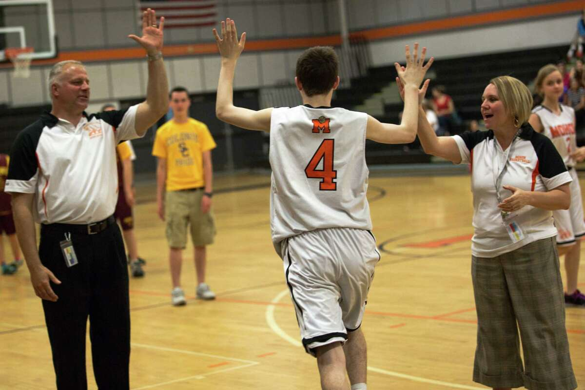 Ben Pierson and Kathleen Wylie, coaches of the Unified Basketball Team high five Justin Smith as he heads out to the court at the Mohonasen Unified Basketball game on May 18, 2015. (Karla Cote / Special to the Times Union)