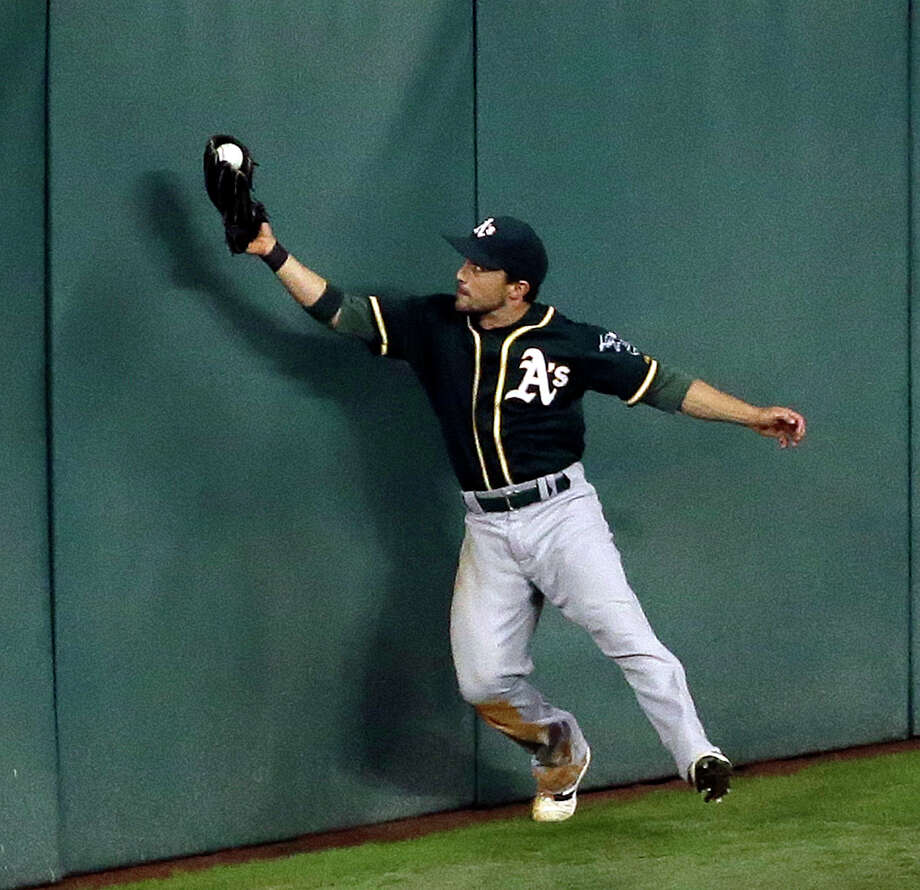Oakland Athletics center fielder Sam Fuld catches a fly ball at the wall hit by Houston Astros' George Springer during the eighth inning of a baseball game Monday, May 18, 2018, in Houston. (AP Photo/David J. Phillip) Photo: David J. Phillip / Associated Press / AP