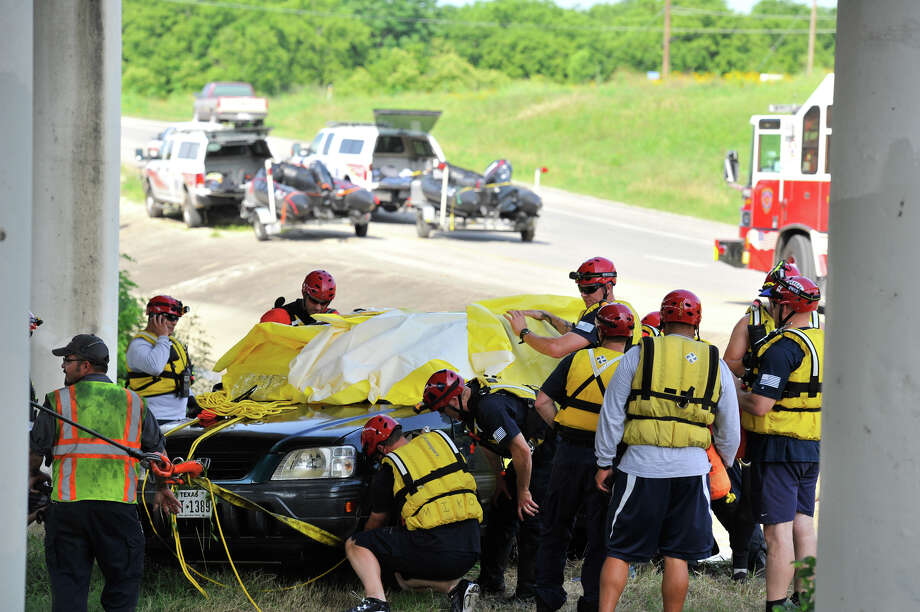 A Fire Department rescue team secures an SUV swept away in the waters of Leon Creek near Interstate 35 and Cassin Road. The SUV went off the road in the morning, and the team recovered the vehicle and the body of a woman inside late in the afternoon. Photo: Photos By Robin Jerstad / San Antonio Express-News