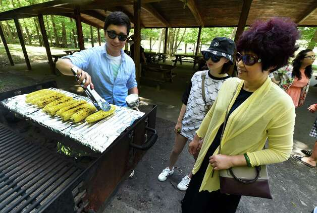 Xiaotong Wei, left, barbecues up some corn on the cob for University of Albany graduate Mengyao Zeng, center, and her mom Shufang Zhang at a party thrown by the I Love NY program Monday afternoon, May 18, 2015, at Thacher Park in New Scotland, N.Y. (Skip Dickstein/Times Union) Photo: SKIP DICKSTEIN / 00031883A