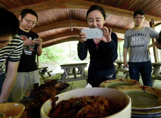 Claudia He makes a photo of the American style barbecue at a party thrown by the I Love NY program Monday afternoon May 18, 2015, at Thacher Park in New Scotland, N.Y.  (Skip Dickstein/Times Union) Photo: SKIP DICKSTEIN / 00031883A