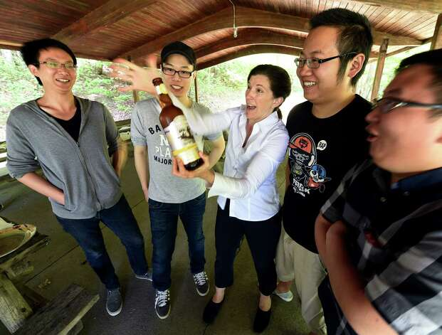 Janet Carmosky, director of the New York State College Towns program, sponsored by I Love NY, pops a cork on some Chinese bubbly at a party for Chinese graduates from the University at Albany and their parents Monday afternoon May 18, 2015 at Thacher Park in New Scotland, N.Y.     (Skip Dickstein/Times Union) Photo: SKIP DICKSTEIN / 00031883A