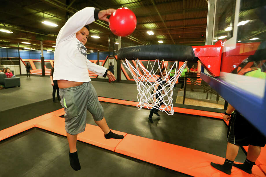 Fabian Espejo, 9, prepares to dunk a ball from a jump on the trampoline at Flip'z Trampoline Park. Photo: Marvin Pfeiffer /San Antonio Express-News / Express-News 2015