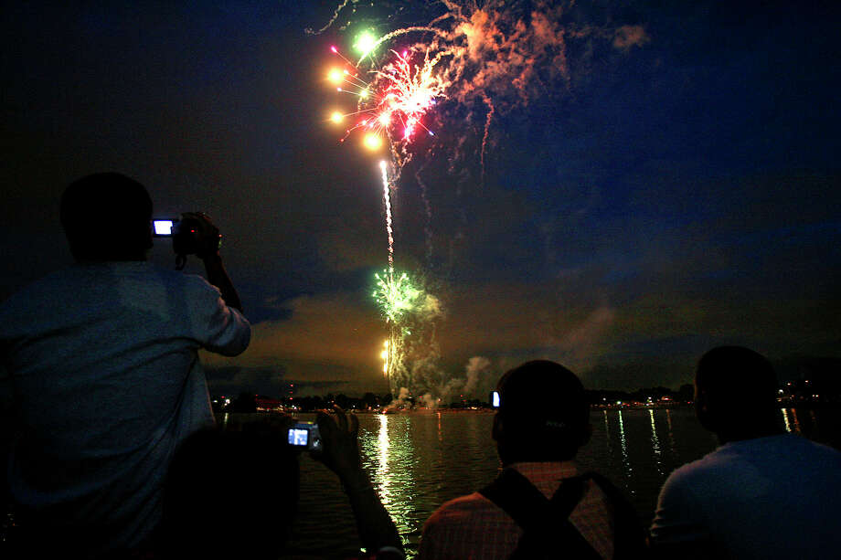 In this 2007 photo, spectators record the start of the Woodlawn Lake fireworks display with camera phones. Photo: Express-News File Photo / SAN ANTONIO EXPRESS-NEWS