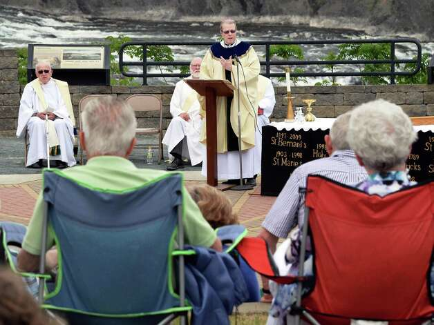 Bishop Edward B. Scharfenberger, center, officiates at the Parish of Holy Trinity outdoor Mass at the Cohoes Falls during Cohoes Heritage Days 2015 Saturday May 16, 2015 in Cohoes, NY.   (John Carl D'Annibale / Times Union) Photo: John Carl D'Annibale / 00031813A