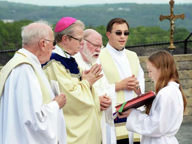 Altar server Lauren Costello, 13, of Cohoes holds a bible for clergymen, from left Lawrence McTavey, retired pastor of St. Bermard's Church, Bishop Edward Scharfenberger, Parish of Holy Trinity deacon Jerry Matthews, and Holy Trinity Pastor James Ebert, during an outdoor Mass at the Cohoes Falls during Cohoes Heritage Days 2015 Saturday May 16, 2015 in Cohoes, NY.   (John Carl D'Annibale / Times Union) Photo: John Carl D'Annibale / 00031813A