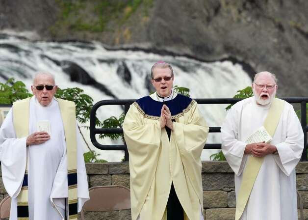 Bishop Edward B. Scharfenberger, center, officiates at the Parish of Holy Trinity outdoor Mass at the Cohoes Falls during Cohoes Heritage Days 2015 Saturday May 16, 2015 in Cohoes, NY. At left is the Rev. Lawrence McTavey, retired pastor of St. Bermard's Church in Cohoes and at right is Parish of Holy Trinity deacon Jerry Matthews.  (John Carl D'Annibale / Times Union) Photo: John Carl D'Annibale / 00031813A