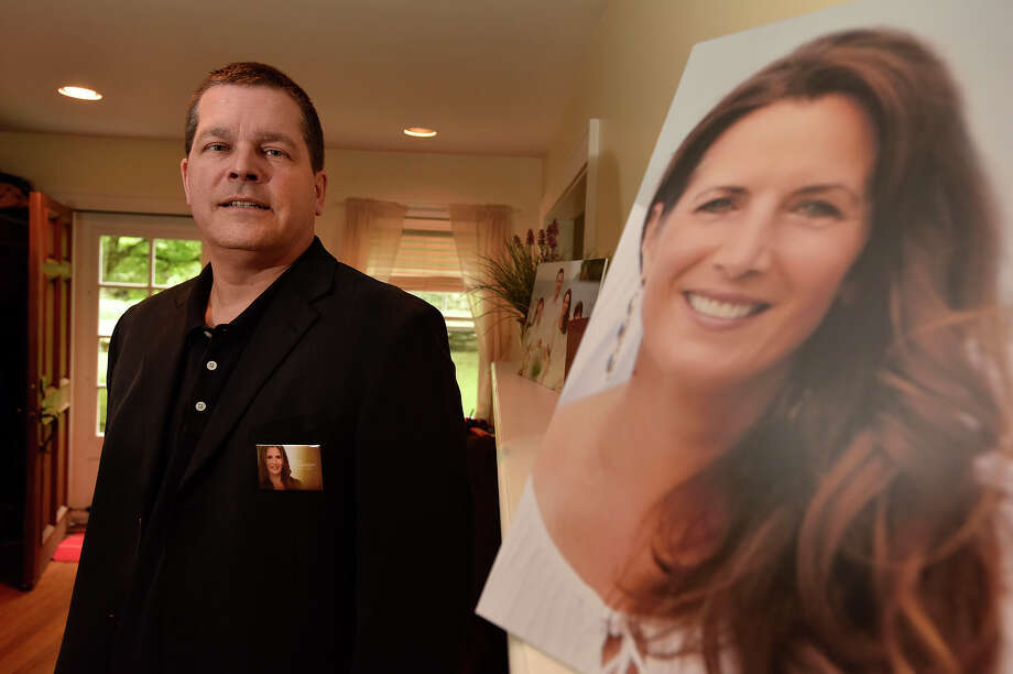"Todd Crawford poses with a photograph of his deceased wife, Lisa Colagrossi - a reporter for WABC in New York City, in their home in Stamford, Conn., on Tuesday, May 19, 2015. Lisa died of a brain aneurysm in March and Todd is helping to lead the charge in bringing awareness and funds to fight the condition by partnering with the Brain Aneurysm Foundation to lobby lawmakers in Washington for more research funding. There are few warning signs that an aneurysm is imminent, ""This is a silent killer,"" says Crawford. Warning signs include intense headaches, blurred vision and vomiting, which can be confused with other less-serious conditions. Photo: Jason Rearick / Stamford Advocate"