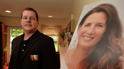 """Todd Crawford poses with a photograph of his deceased wife, Lisa Colagrossi - a reporter for WABC in New York City, in their home in Stamford, Conn., on Tuesday, May 19, 2015. Lisa died of a brain aneurysm in March and Todd is helping to lead the charge in bringing awareness and funds to fight the condition by partnering with the Brain Aneurysm Foundation to lobby lawmakers in Washington for more research funding. There are few warning signs that an aneurysm is imminent, """"This is a silent killer,"""" says Crawford. Warning signs include intense headaches, blurred vision a"""