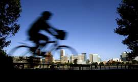 FILE - In this July 10, 2008, file photo, a bicyclist travels along the east bank of the Willamette River as the downtown skyline is bathed in early morning sunlight in Portland, Ore.  Oregon lawmakers want kids, and adults, wearing helmets when they ride their bikes. One bill would require people under 18 to wear a helmet while riding a bicycle, skateboard or scooter or using in-line skates or roller skates, on public or private land while another bill would require everyone to wear a helmet when participating in organized bike rides or races. (AP Photo/Don Ryan, File)