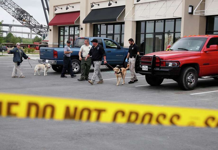 Law enforcement officers use dogs to search cars in a Waco, Texas, parking lot that was the scene of a deadly clash among several motorcycle gangs Sunday. Photo: Rod Aydelotte / Associated Press / Waco Tribune-Herald