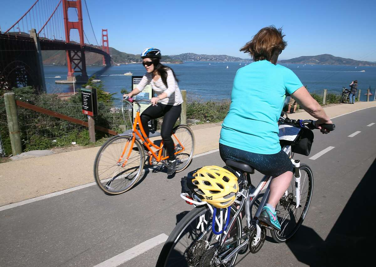 A bicycle rider rolls past the Golden Gate Bridge with her helmet strapped to the back in San Francisco, Calif. on Saturday, Feb. 14, 2015. A bill has been introduced in the state legislature that would make helmets mandatory for all bicycle riders, requiring adults to wear them in addition to minors. **MANDATORY CREDIT FOR PHOTOG AND SF CHRONICLE/NO SALES-MAGS OUT-TV OUT**