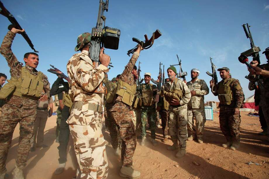 Shiite militia fighters hold up their weapons in Nukhayb village in the embattled Anbar province. Photo: Mohammed Sawaf / AFP / Getty Images / AFP