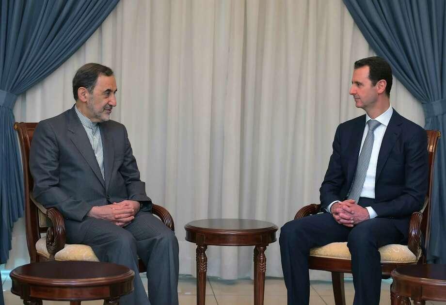 President Bashar Assad (right) meets in Damascus with Ali Akbar Velayati, an adviser to Iran's Supreme Leader Ayatollah Ali Khamenei. Photo: Uncredited / Associated Press / SANA