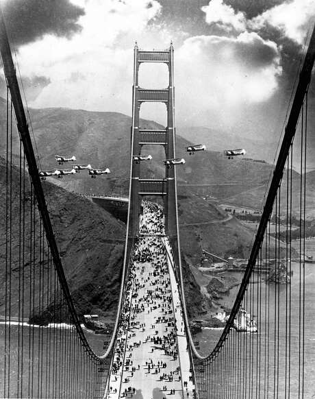 GGBRIDGE-B-1937-MN-CHRONICLE - Opening day of the Golden Gate Bridge, 1937. Pedestrians walk on the brdige, while planes fly between the North and South Towers of the bridge during opening day.  Chronicle File Photo Photo: Chronicle File Photo