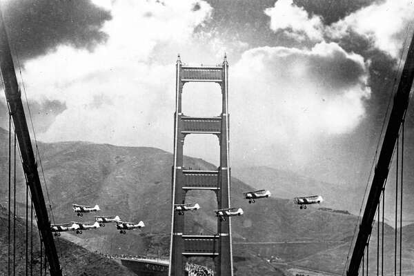 GGBRIDGE-B-1937-MN-CHRONICLE - Opening day of the Golden Gate Bridge, 1937. Pedestrians walk on the brdige, while planes fly between the North and South Towers of the bridge during opening day.  Chronicle File Photo
