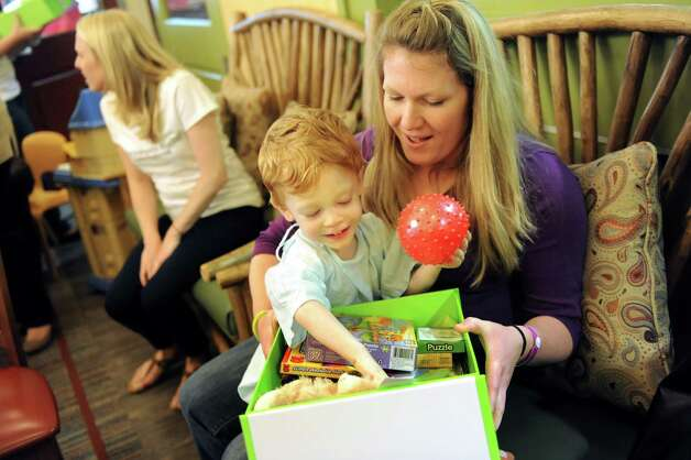 John Cuthbertson, 3, of Waterford and his mother, Katie Cuthbertson, go through a box of Cheeriodicals on Tuesday, May 19, 2015, at the Albany Medical Center in Albany, N.Y. Cheeriodicals are green boxes filled with gifts from Northwestern Mutual employees and consist of age-appropriate magazines, toys and crafts for young patients. (Cindy Schultz / Times Union) Photo: Cindy Schultz / 00031891A