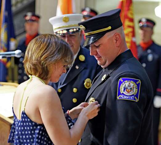 Newly promoted lieutenant Steven Disick has his new badge pined on by girlfriend MarryEllen Torrisi under the watchful eye of Chief Warren Abriel, background,  during promotion ceremony for four Albany firefighters in the rotunda of Albany City Hall May 19, 2015 in Albany, N.Y.  One Lieutenant was promoted to Captain and three firefighters were promoted to Lieutenant.      (Skip Dickstein/Times Union) Photo: SKIP DICKSTEIN / 00031903A