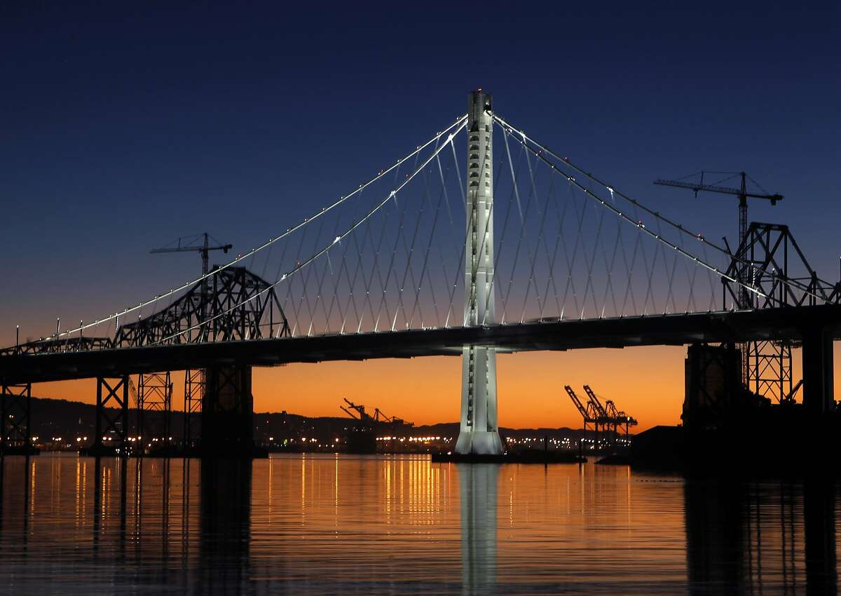 The new eastern span of the Bay Bridge is illuminated at daybreak in San Francisco, Calif. on Tuesday, Dec. 23, 2014.