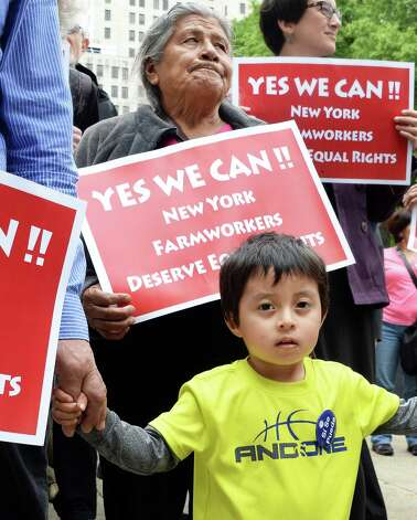 Former farm worker Isabel Rojas, top, and her grandson Axel Rodriguez, 3, of Brockport march with advocates for New YorkOs farmworkers calling for the passage of the Farmworkers Bill of Rights, to the Capitol Tuesday May 19, 2015, in Albany, NY.  (John Carl D'Annibale / Times Union) Photo: John Carl D'Annibale / 00031901A