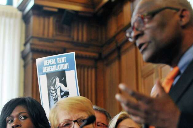 A supporter of rent regulation holds up a sign behind Assembly Democrats as they hold a press conference on rent regulations at the Capitol on Tuesday, May 19, 2015, in Albany, N.Y.  (Paul Buckowski / Times Union) Photo: PAUL BUCKOWSKI / 00031902A