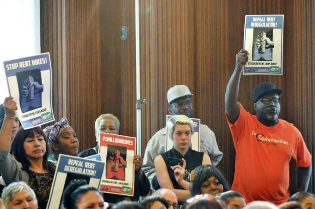 Supporters of rent regulations hold up signs at a press conference on rent regulations at the Capitol on Tuesday, May 19, 2015, in Albany, N.Y.  (Paul Buckowski / Times Union) Photo: PAUL BUCKOWSKI / 00031902A