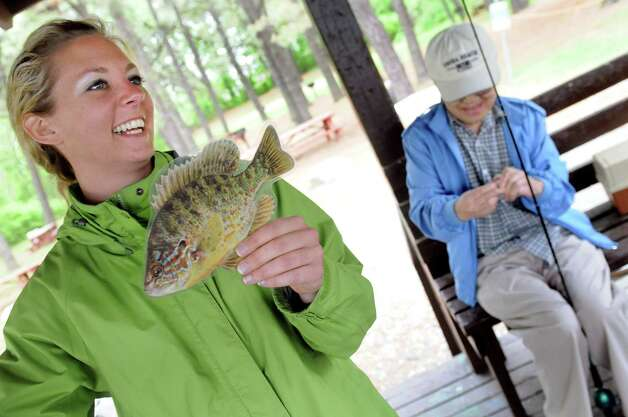 Fish biologist Joelle Ernst, left, holds a cutout of a Pumpkin Seed Sunfish while talking about the fish in Rensselaer Lake during a Department of Environmental Conservation Free Sport Fishing Clinic on Tuesday, May 19, 2015, at Six Mile Waterworks in Albany, N.Y. At right is Ted Yoshinari of the Colonie Seniors. The clinics, which are held across the state, allow would-be-fishing enthusiasts the chance to receive instruction and try the sport without a license. For more information visit www.dec.ny.gov. (Cindy Schultz / Times Union) Photo: Cindy Schultz / 00031852A