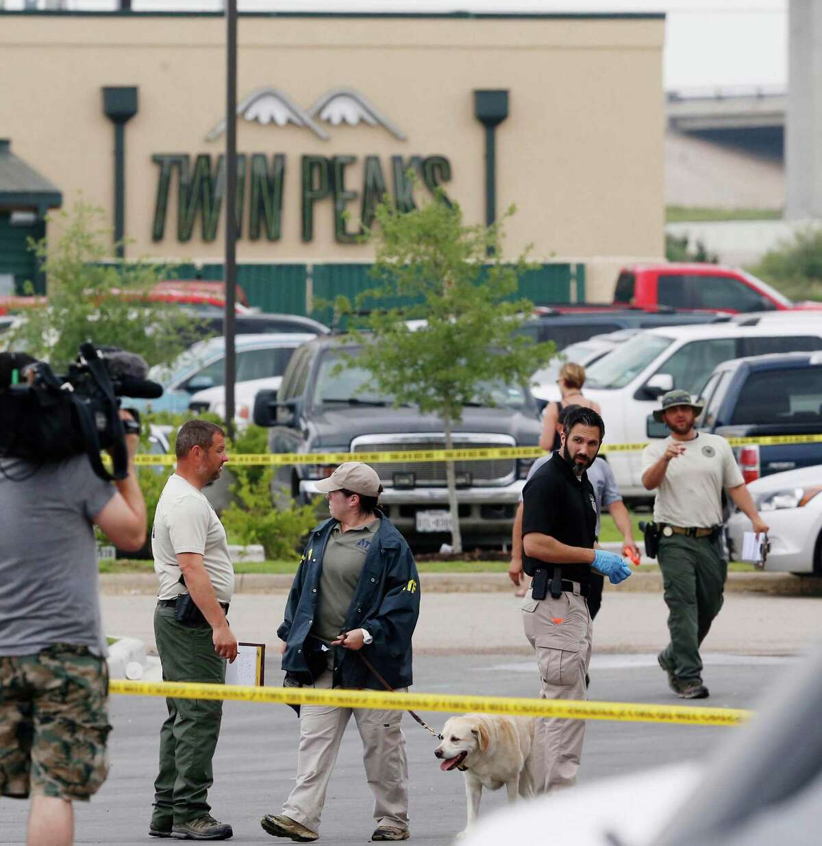 Law enforcement officers use a dog to search parked cars located in part of the Central Texas Marketplace Tuesday, May 19, 2015, in Waco, Texas. A deadly weekend shootout involving rival motorcycle gangs apparently began with a parking dispute and someone running over a gang member's foot, police said Tuesday. One man was injured when a vehicle struck his foot. That caused a dispute that continued inside the restaurant, where fighting and then shooting began, before spilling back outside, Waco police Sgt. W. Patrick Swanton said. The shootout left nine people dead injured 18 wounded. (Rod Aydelotte/Waco Tribune-Herald via AP)