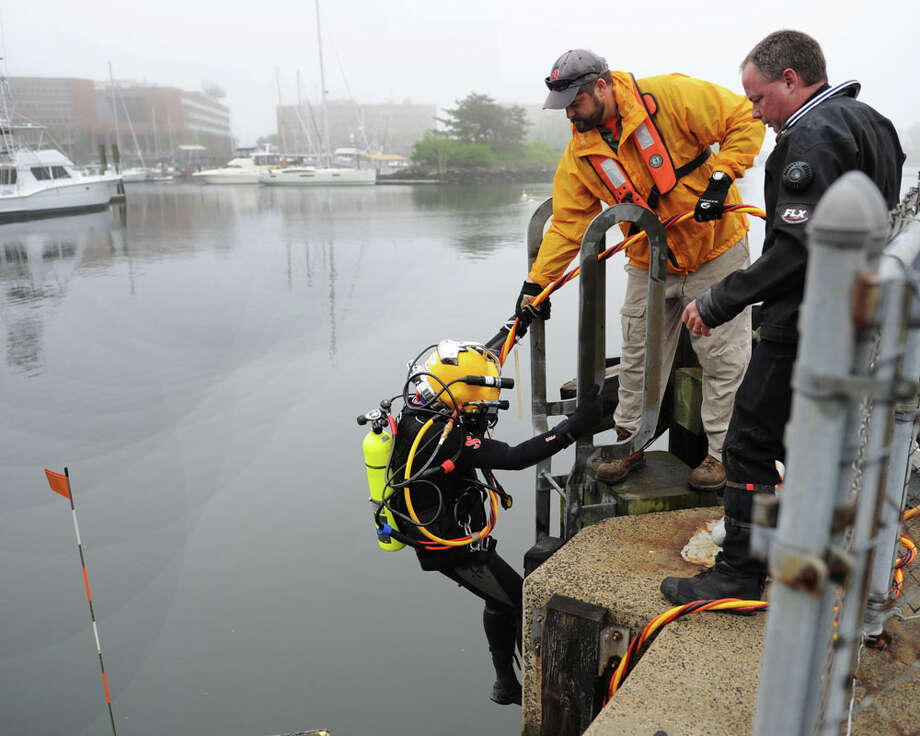 Diver Ed Gawerecki, left, gets assistance from tender Byron Rupp, center, and standby diver Steve England before the dive at Stamford's hurricane barrier near Kosciuszko Park in Stamford, Conn. Tuesday, May 19, 2015.  The U.S. Army Corps of Engineers did a dive to examine the condition of the hurricane barrier and determine which parts need to be replaced in another dive later this year. Photo: Tyler Sizemore / Greenwich Time