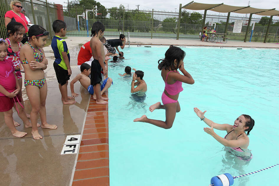 In this 2012 photo, Guadalupe Duran, 6, jumps into the arms of lifeguard Taylor Spain at Lady Bird Johnson Park's swimming pool.