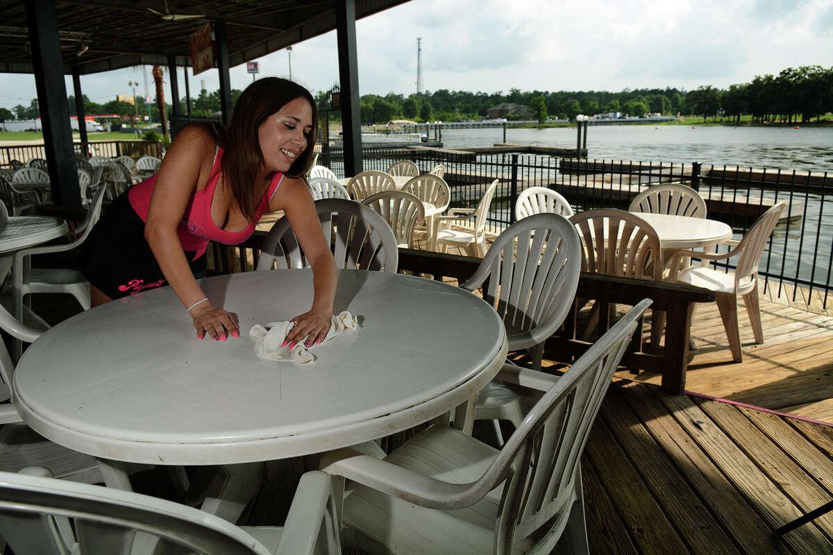 Waitress Natasha Johnson, 21, of Lake Conroe, wipes down tables at Papa's on the Lake after a rainy morning on Monday, May 18, 2015. (Photo by Jerry Baker/Freelance)