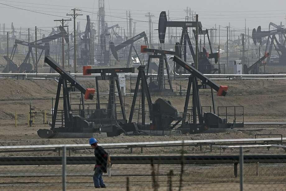 A person walks past pump jacks operating at the Kern River Oil Field in Bakersfield, Calif. (AP Photo/Jae C. Hong, File) Photo: Jae C. Hong, Associated Press