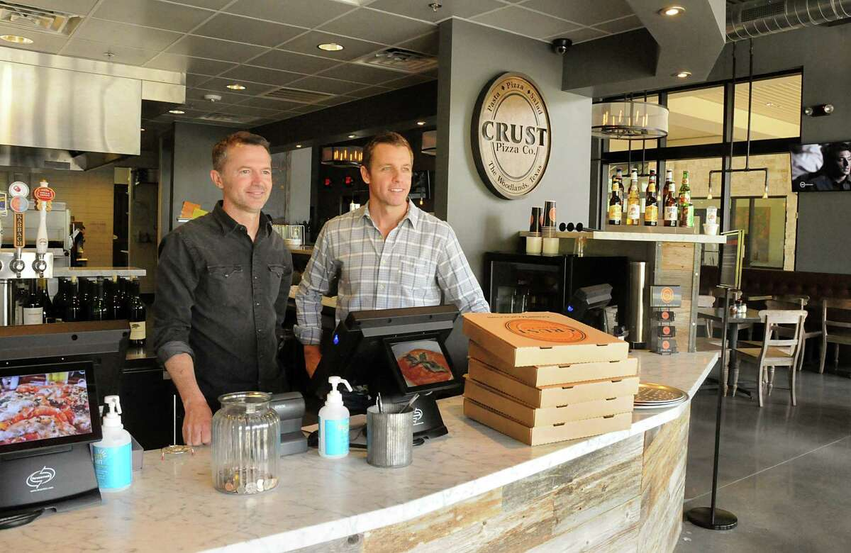 Crust Pizza owners Mark Rasberry and Clint Price wait for a customer to pick up an order at the new Crust Pizza in the Creekside Park Village Center, This is the third Crust Pizza to open in The Woodlands.