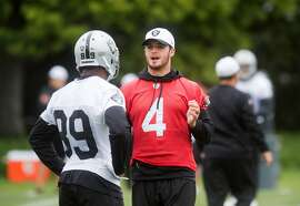 Derek Carr, right, speaks with Amari Cooper during an Oakland Raiders workout on Tuesday, May 19, 2015, in Alameda, Calif. (AP Photo/Noah Berger)