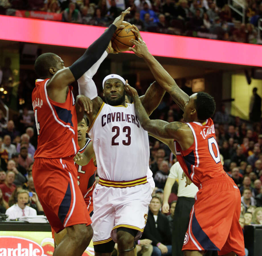 LeBron James (center), driving between Atlanta's Paul Millsap (left) and Jeff Teague, had 32 points and seven assists in the Cavaliers' 127-94 rout of the Hawks on Nov. 15. Photo: Mark Duncan / Associated Press / AP