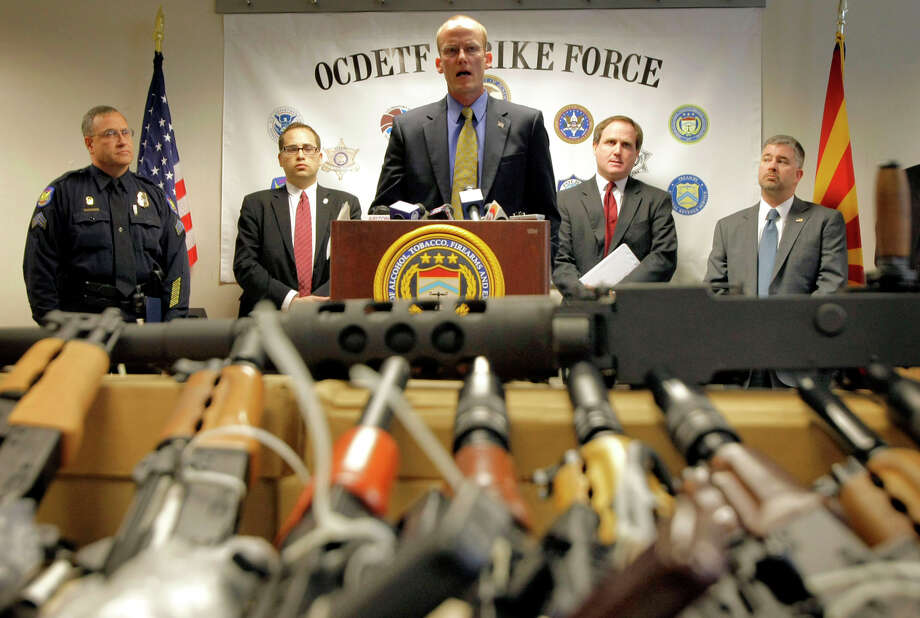 "Phoenix ATF agent Bill Newell speaks in 2011 behind a cache of seized weapons. At the time, the ATF was under fire over a gun-trafficking investigation called ""Fast and Furious."" Photo: Matt York / Matt York / Associated Press 2011 / AP"