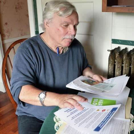 Ed Landing, a retired state geologist and a victim of identity theft, looks over documents he's put together as he tries to get back his stolen IRS federal tax return refund Wednesday, May 13, 2015, in Albany, N.Y.  (John Carl D'Annibale / Times Union) Photo: John Carl D'Annibale / 00031830A