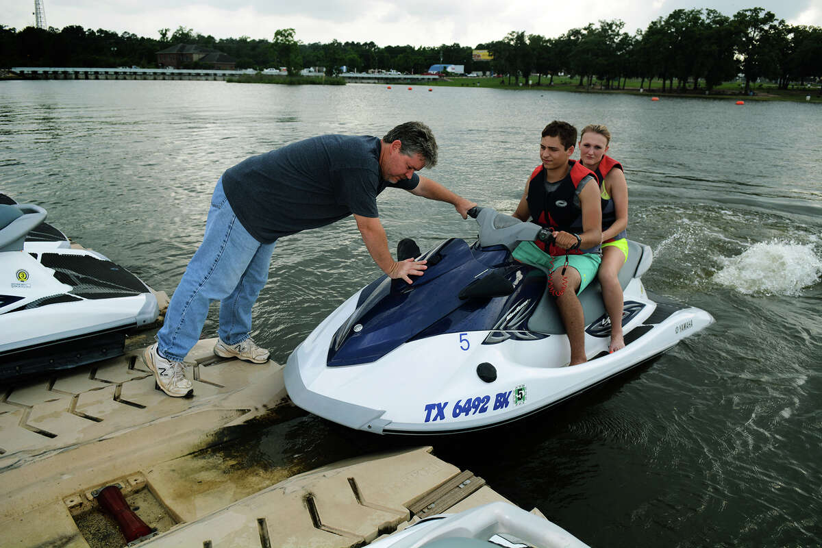 Don Beckham of Lake Conroe Water Sports,helps customers. Some lake residents oppose plans to use the lake for area water needs.