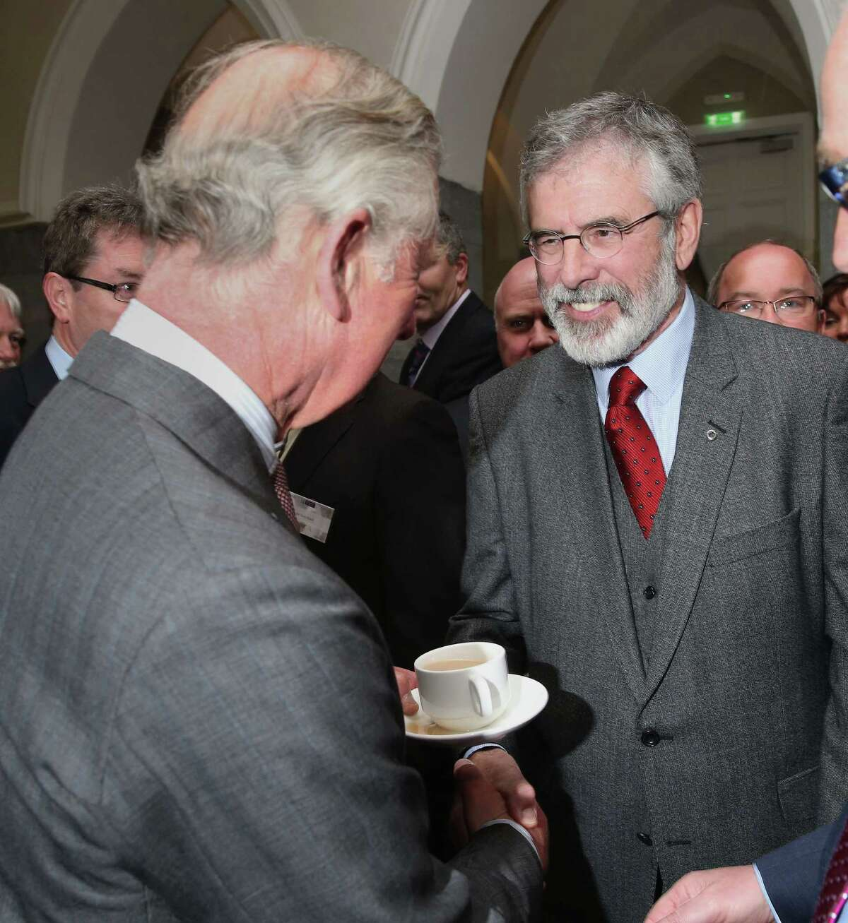 Britain's Prince Charles. left, shakes hands with Sinn Fein president Gerry Adams at the National University of Ireland in Galway, Ireland, Tuesday May 19, 2015. Prince Charles has begun an official visit to Ireland featuring two new milestones of peacemaking: his first meeting with leaders of the Irish nationalist Sinn Fein party, and his first trip to the fishing village where the Irish Republican Army killed his great-uncle 36 years ago. It is Charles' third trip to the Irish Republic since the outlawed IRA called a 1994 cease-fire. (Brian Lawless/Pool photo via AP)