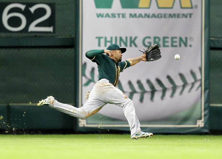 HOUSTON, TX - MAY 19:  Coco Crisp #4 of the Oakland Athletics can't track down this line drive off the bat of Colby Rasmus of the Houston Astros in the second inning at Minute Maid Park on May 19, 2015 in Houston, Texas.  (Photo by Bob Levey/Getty Images) Photo: Greg Fiume / Getty Images / 2015 Getty Images