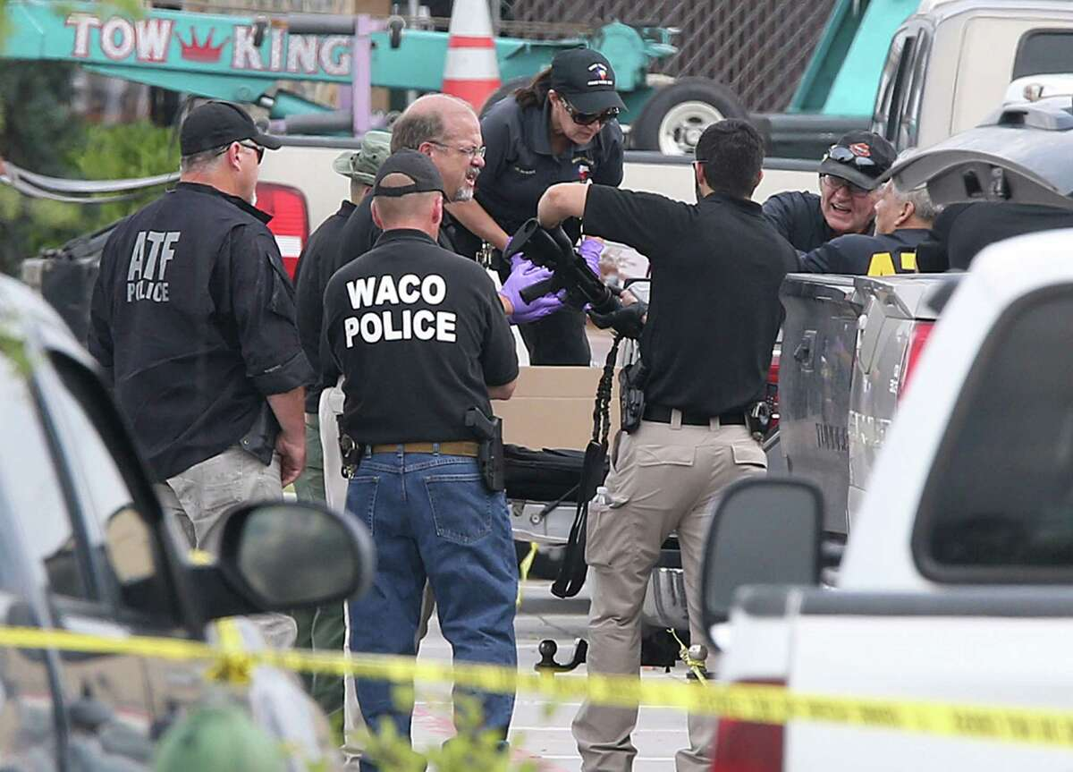 Police investigators recover a weapon from a vehicle in the Twin Peaks parking lot Tuesday in Waco.