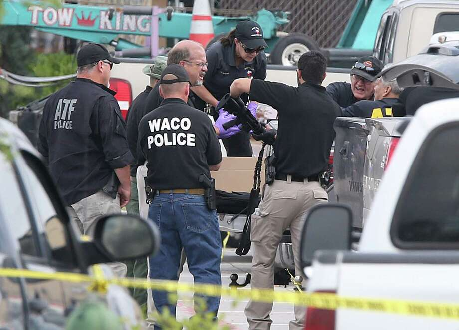 Police investigators recover a weapon from a vehicle in the Twin Peaks parking lot Tuesday in Waco. Photo: Jerry Larson, MBO / Waco Tribune-Herald