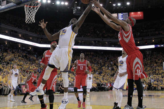 Warrior Draymond Green (23) and Rockets Corey Brewer go after a rebound during Game 1 of the Western Conference Finals on Tuesday, May 19, 2015 in Oakland, Calif.