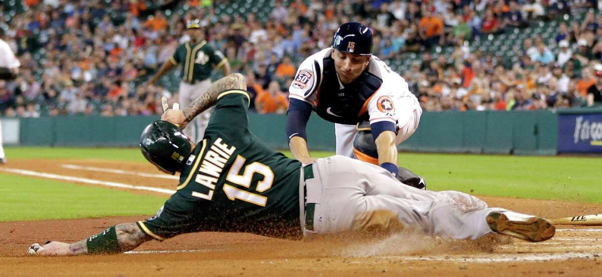 Astros catcher Jason Castro finishes off a busy second inning by tagging out the Athletics' Brett Lawrie, who was trying to score from second base on an infield hit. It was the second out the Astros recorded at home in the inning.