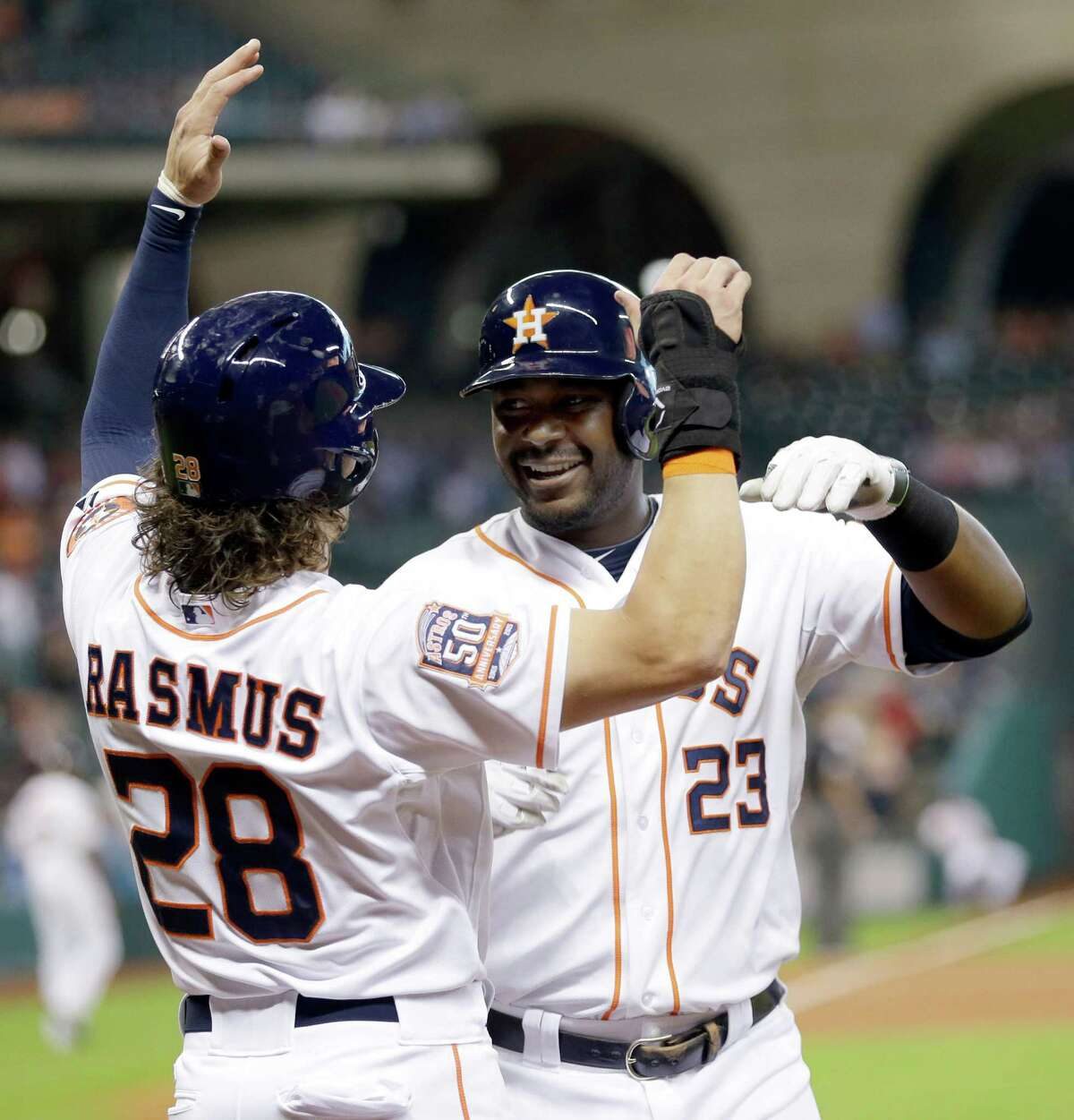 Houston Astros' Chris Carter (23) celebrates his two-run home run with Colby Rasmus (28) during the second inning of a baseball game against the Oakland Athletics on Tuesday, May 19, 2015, in Houston. (AP Photo/David J. Phillip)